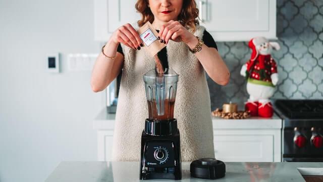 Nainen laittaa jauhetta blenderiin